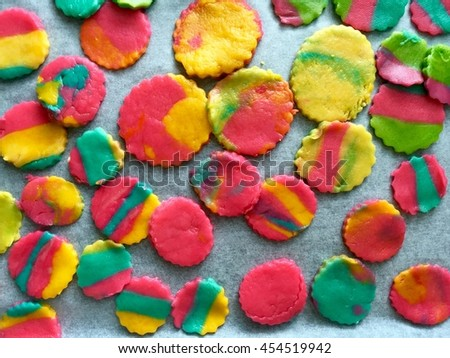 Many different size of cycle rainbow cookies dough in pink yellow and green colors made by kindergarten children on stencil paper on tray - stock photo