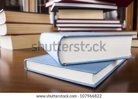 Many different sized colored and shaped books on wood table - stock photo