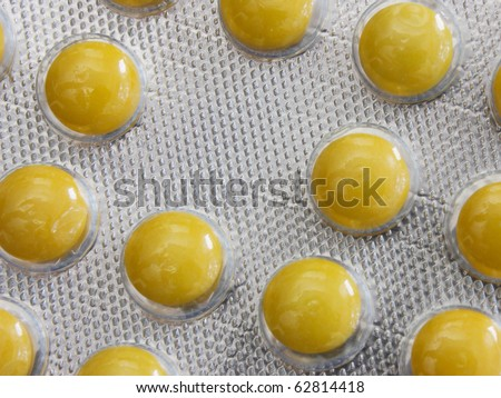 Many different tablets lie on a white background of yellow color. - stock photo