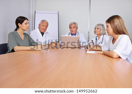 Many doctors sitting in a team meeting on a round table
