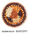 Many dried fruits on a round plate with hazel, cashew nuts, prunes, figs, raisin and apricots isolated on white - stock photo