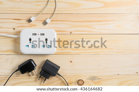 Many electrical plugs connected to a power  on wooden table - stock photo