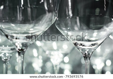 Many elegant wine glasses standing side by side. Background lighting creating emotional effect.