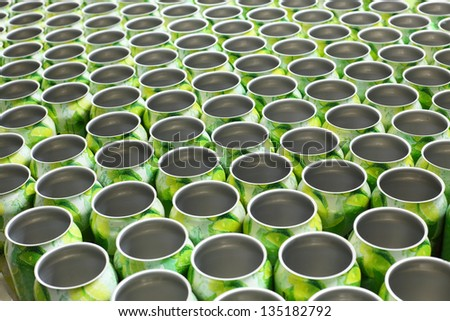 Many empty aluminum cans for drinks move on conveyor at big factory. - stock photo