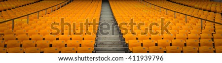 Many empty seats in rows in an outdoor sports stadium - stock photo