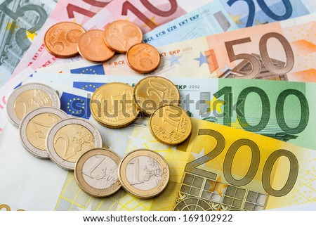 Many euro banknotes and coins - stock photo