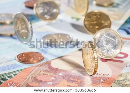 Many euro banknotes and coins - closeup shot - stock photo