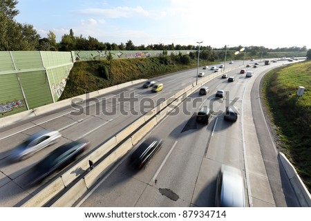 many fast cars on a busy highway. - stock photo