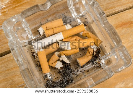 Many  filter cigarette butts filling a small ashtray - stock photo