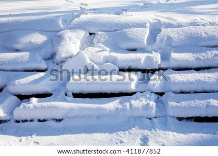 Many footprints on the snowy stairs - stock photo