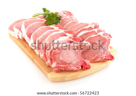 Many fresh pork chops or cutlets with parsley - stock photo