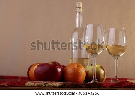 Many fresh ripe red green apples and orange fruits lying on checkered plaid near bottle and two goblets with white wine standing on wooden table top on paper background copyspace, horizontal picture - stock photo