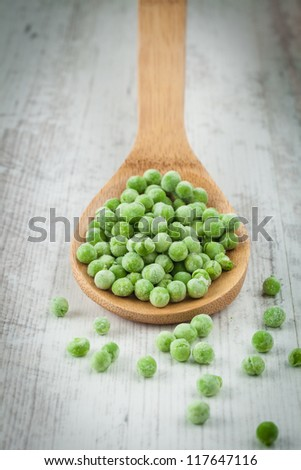 Many frozen green peas on a wooden spoon - stock photo