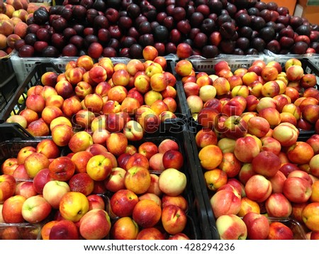 Many fruits nectarines and plums lying in boxes in supermarket