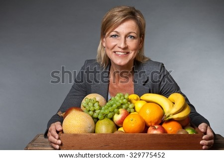 Many fruits stacked together and cute woman bearing them - stock photo
