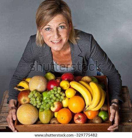 Many fruits stacked together and cute woman bearing them