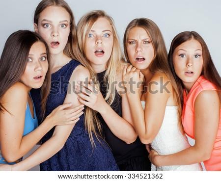 many girlfriends hugging celebration on white background, smiling talking chat, girl next door close up wondering - stock photo