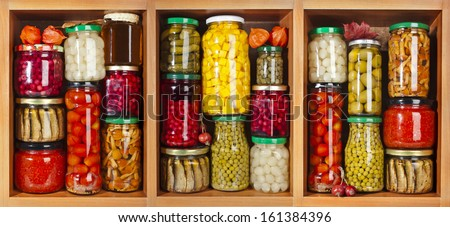 many glass bottles with preserved food set in wooden cabinet - stock photo