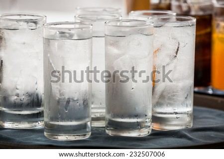 many glass of ice water are on a tray