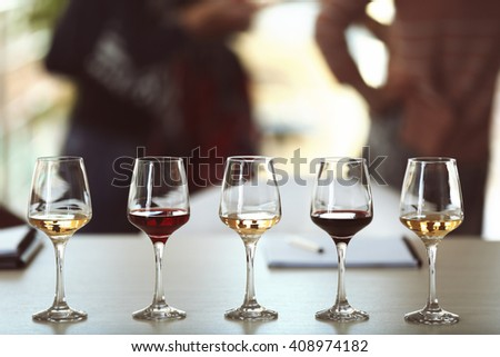 Many glasses of different wine in a row on a table. Tasting wine concept - stock photo