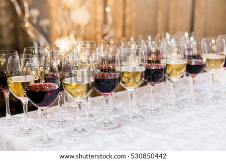Many glasses with white and red wine on buffet table. Soft focus, selective focus