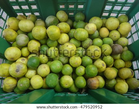 Many Green and Yellow Lemons Put Together in the Green Plastic Basket