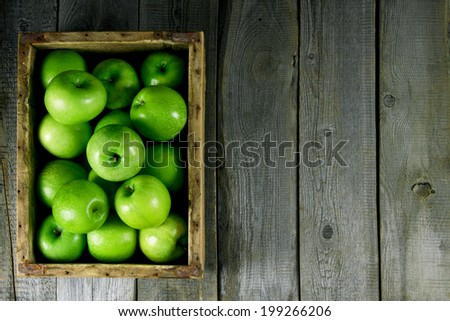 Many green apples in an old box. On a wooden background. - stock photo