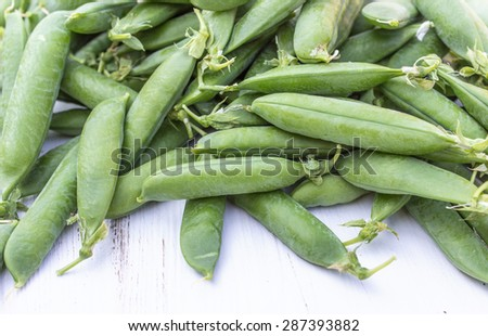 many green pea pods / fresh peas / vegetables