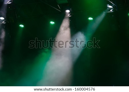 many green spotlights that illuminate the stage at a concert with fog