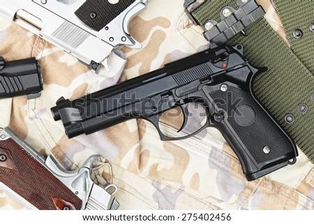 Many Guns on Military texture. Handguns on camouflage background. 9mm, 11mm Pistols. - stock photo