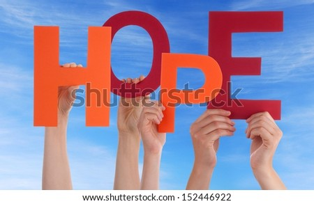 Many Hands Holding a Colorful Hope in Front of a Sky - stock photo