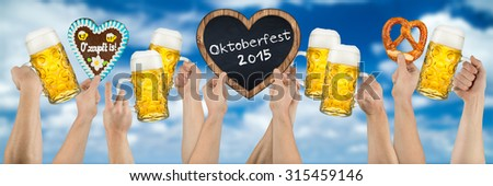 many hands holding german oktoberfest beer heart shaped gingerbread and blackboard on blue cloudy sky - stock photo