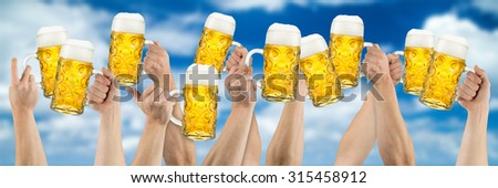 many hands holding german oktoberfest beer on blue cloudy sky - stock photo