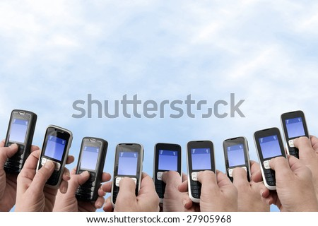 Many hands holding mobile phones with empty text message boxes in the lower part of the image - stock photo