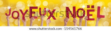 Many Hands Holding the French Words Joyeux Noel Which Means Merry Christmas on a Golden Background - stock photo