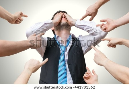 Many hands pointing at disappointed man and blame him. - stock photo