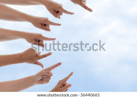 Many hands pointing to the right with a blue sky in the background