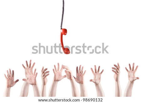 Many hands raised upward reach for the handset. - stock photo
