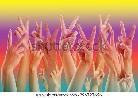 many hands showing victory sign, pride colors - stock photo