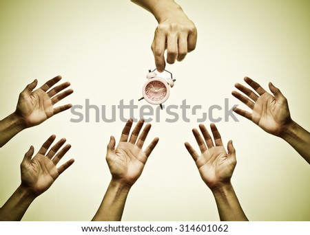Many hands trying to reach a clock - Time is important. - stock photo