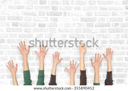 Many hands up on the background of a brick wall - stock photo
