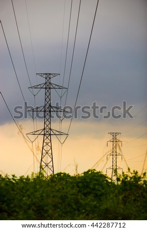 Many high voltage electric pole with yellow sky, vertical picture