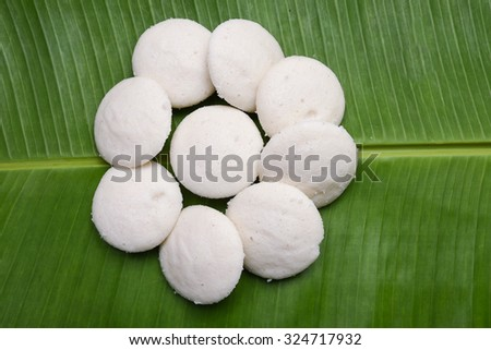 Many Idlis  /idly arranged in flower shape on plantain leaf in Kerala, India. served with vegetarian side dish Sambar, coconut chutney, pure ghee. made by batter of fermented black lentils and rice.