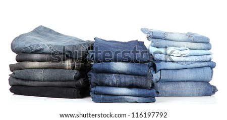 Many jeans stacked in a piles isolated on white - stock photo