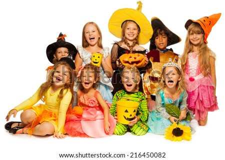Many kids sit in group wearing Halloween costumes - stock photo
