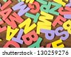 many letters of different colors are on a wooden surface - stock photo