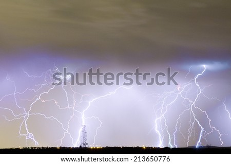 Many lightning bolts striking on the horizon with a communication tower.  - stock photo