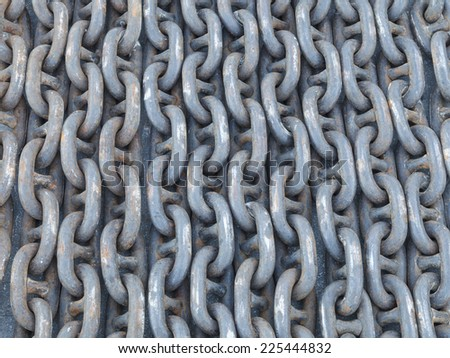Many lines of used rusty heavy iron chain on the ground. - stock photo