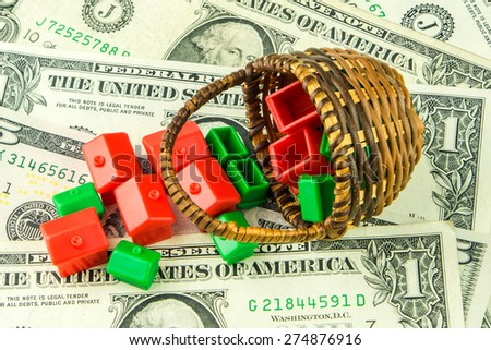 Many little green and red houses made of plastic are laying on one dollar banknote - stock photo