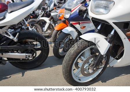 many motorcycles on parking on asphalt  close up